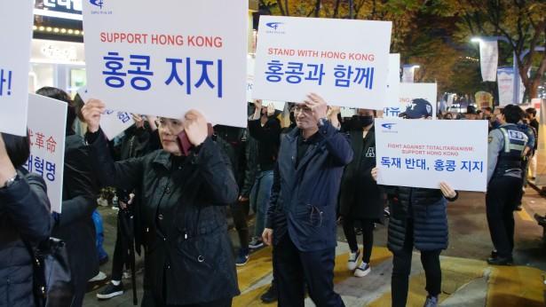 """主办方拉着写有""""SOS HK""""的横幅走在前面"""