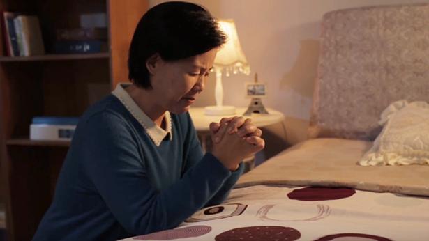 一个中年姊妹在房间祷告