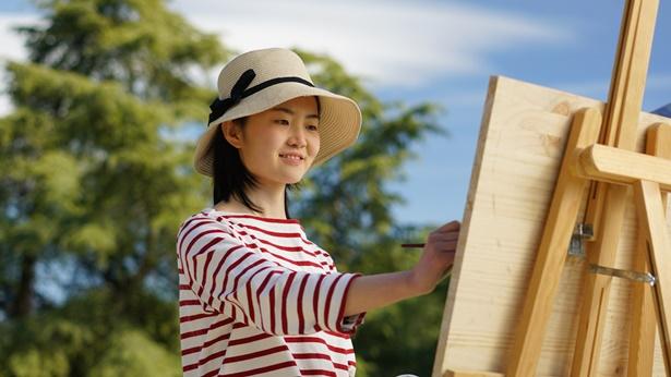 一个年轻女孩在户外画画