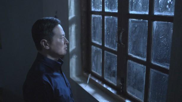 一名基督徒表情沉重的看着窗外