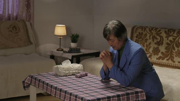 姊妹跪在桌前跟神祷告