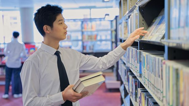 一个年轻的男士在图书馆书架前找书