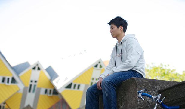 男孩坐在橋邊思考
